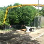 Concrete boom pump extended into difficult access site