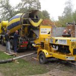 Trailer-mounted pump transporting ready-mix concrete through a static line