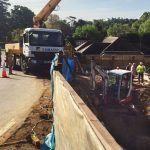 SCHWING 24m concrete boom pump — pumping down from road to construction site